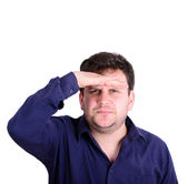Portrait of a young chubby serious man with hand to head peering — Stock Photo
