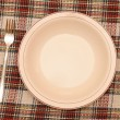 Knife, white plate and fork on red checked tablecloth — Stock Photo #13165276