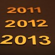 Upcoming years 2011, 2012 and 2013 as golden digits over dark b — Stock Photo #13262503