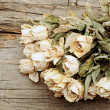 Stock Photo: Bouquet dried roses on old wood background with copy space