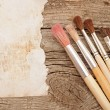 Paint brushes on old wooden background with blank vintage paper — Stock Photo