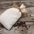 Coffee beans and burlap sack on wooden background — Stock Photo