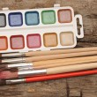 Foto Stock: Paints and brushes on wooden table