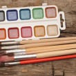 Paints and brushes on wooden table — Stockfoto #14032199