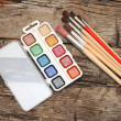 Paints and brushes on old wooden table — Stock Photo