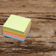 Vibrant block of colorful post it notes on wooden background — Stock Photo