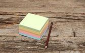 Nota de papel y lápiz sobre fondo de madera — Foto de Stock