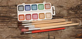Paints and brushes on wooden table — Stock Photo