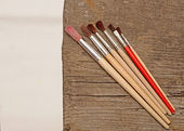 Paint brushes on old wooden background with white canvas — Stock Photo