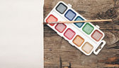Water-color, brush and palette with canvas on old wooden backgro — Stock Photo