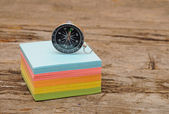 Colorful post it note block with compass on wood table — Stock Photo