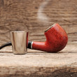 Stainless glass of cognac and tobacco pipe on old wooden backgro - Foto Stock