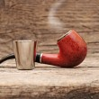 Stainless glass of cognac and tobacco pipe on old wooden backgro - Photo