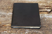 Black leather notebook on wooden background — Stock Photo