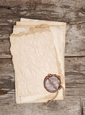 Stack of old papers with a wax seal on wooden background — Stock Photo