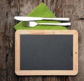 Quadro de menu deitado na mesa de madeira velha com faca e garfo — Fotografia Stock