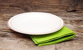 Empty white plate on wooden table — Stock Photo