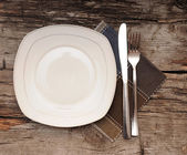 Empty dish, knife and fork and brown napkin on old wood table — Stock Photo