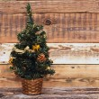 Christmas fir tree with decoration on a wooden background — Stok fotoğraf