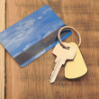 Key with plastic card and reflection blue sky and clouds — Stock Photo