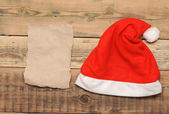 Santa cap on grunge blank sheet of paper — Stock Photo