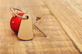 The key with Christmas ball on wooden background — Stock Photo