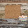 Empty cork board with colorful stack note papers against wooden — Stock Photo