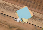Note paper and home keys with blank tag on wood background — 图库照片