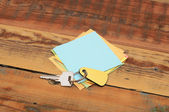 Clean post-it note on a wood background with a key — Stock Photo