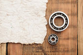 Steel ball bearings with old paper on wooden table. space for yo — Stock Photo