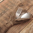 Knife and fork in rough old sacking over wood — Stockfoto