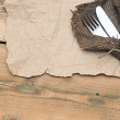 A place setting with silver fork and knife on old sacking textur — Stock fotografie
