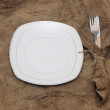 Empty white plate fork and knife on brown sacking texture — Stock Photo #14430557