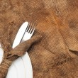 A place setting with silver fork and knife on old sacking textur — Stock Photo