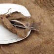 A place setting empty plate, silver fork and knife on old sackin — Стоковая фотография