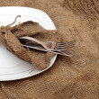 A place setting empty plate, silver fork and knife on old sackin — Stock Photo