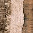 Old paper with natural burlap on wooden backround - Stock Photo