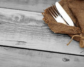 Knife and fork in rough old sacking over wood — Stock Photo