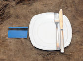 Empty plat, fork and knife on old sacking texture — Stock Photo
