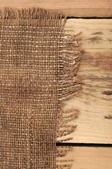 Burlap hessian sacking on wood background — Stock Photo