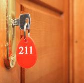 Dveřní kliky na dřevěné křídlo dveří a klíč v klíčové dírky s číslem — Stock fotografie