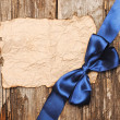 Blue bow on blank old paper with copyspace for your text — Stock Photo