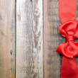 Red bow and ribbon on the old wooden background — Stock Photo #14875263