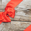 Photo: Red bow on wood background