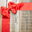 Red bow and ribbon on the old wooden background — Stock Photo #14875343