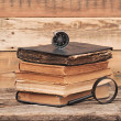Stack of antique books with compass and magnifying glassl on woo — Stockfoto
