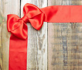 Red bow and ribbon on the old wooden background — Stock Photo