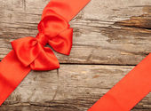 Red bow and ribbon on the wooden background — Stock Photo