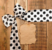 White bow with black dot on wooden background with copyspace for — Stock Photo