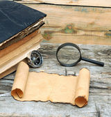 Stack of antique books with compass, magnifying glass and paper — Stock Photo